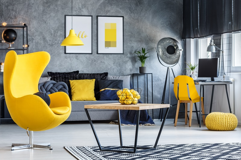 Hipster room with accent chair table, yellow designer armchair and concrete walls