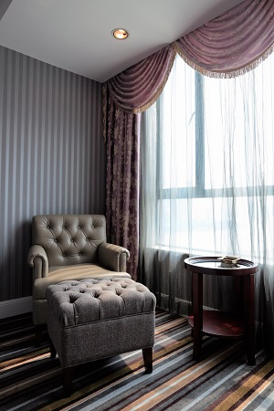 a chair and ottoman next to a window